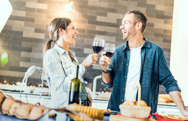 Young couple in love drinking red wine at house kitchen - Happy millenial people at home enjoying aperitif time cheering together at jubilee anniversary - Genuine youth concept on bright indoor filter stock photo