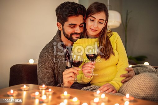 A young couple is at home, they are enjoying their free time and drinking wine