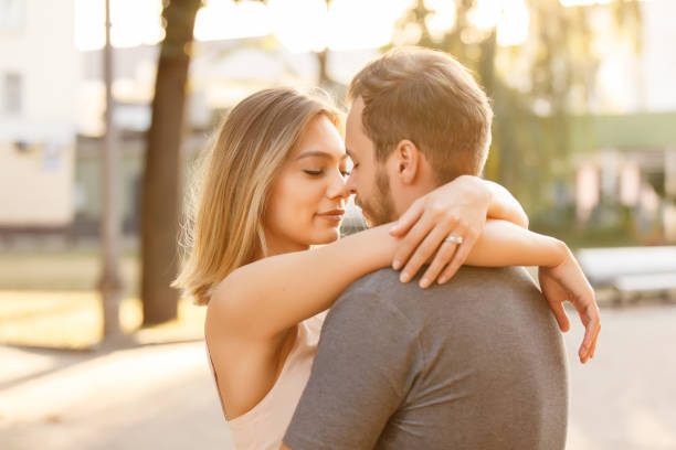 Young couple in love embracing in the city at sunset Young couple in love embracing in the city at sunset falling in love stock pictures, royalty-free photos & images