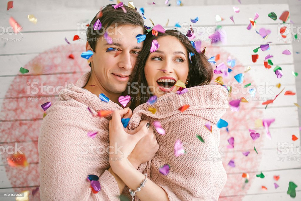 Young couple in love embracing under confetti in decorated studi – Foto