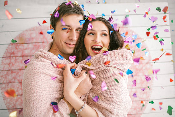 Young couple in love embracing under confetti in decorated studi stock photo