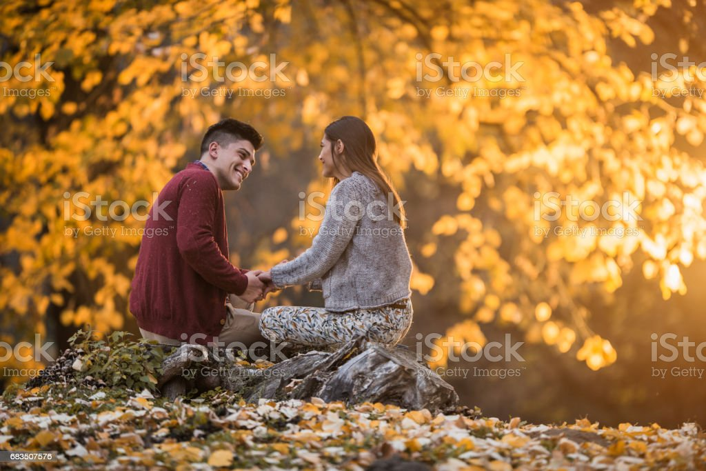 Young couple in love enjoying in a conversation at the park. stock photo