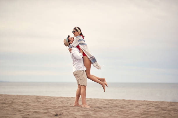 Young couple in love have fun on the beach stock photo