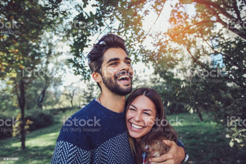 Young couple in love having fun at park stock photo