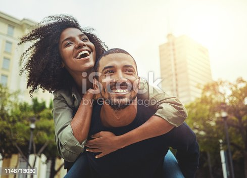 Cheerful young man giving piggyback ride to his girlfriend outdoors in the city