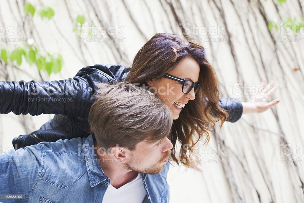 Young couple in love having fun on a Berlin park royalty-free stock photo
