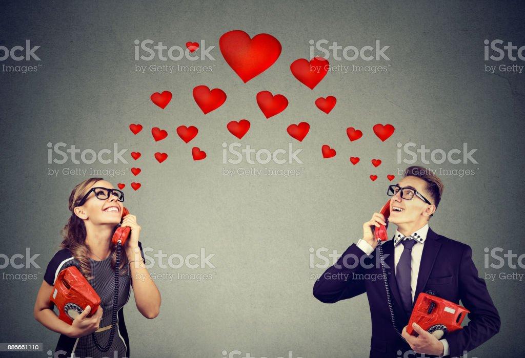 Jeune couple amoureux ayant conversation téléphonique romantique - Photo