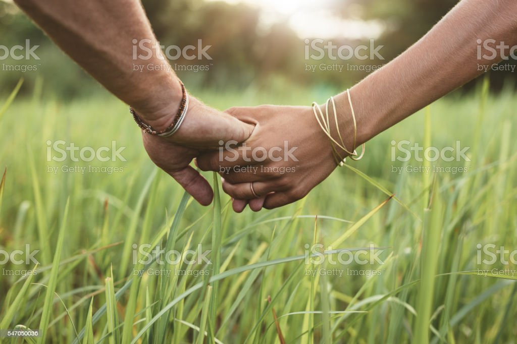 Young couple in love holding hands stock photo