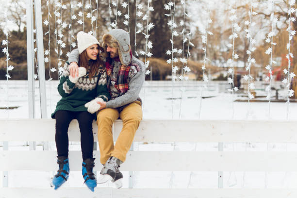 Young couple in love is enjoying winter day skating Young couple in love is enjoying winter day skating and flirting. Copy space. ice skating stock pictures, royalty-free photos & images