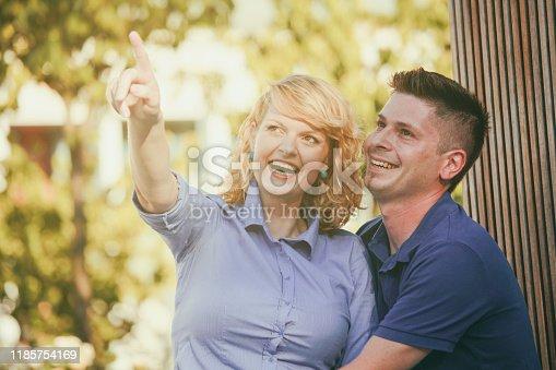 Woman showing something to his boyfriend on a park bench. Young couple in love enjoying relaxing summer afternoon.