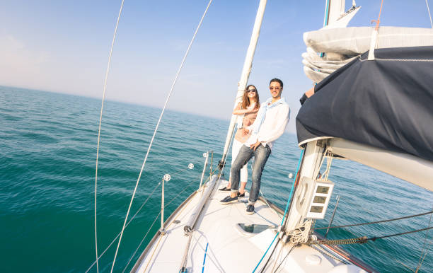 Young couple in love on sail boat having fun with champagne flute glasses - Happy exclusive travel concept on sailboat tour - Boyfriend and girlfriend on luxury cruise - Sunny afternoon color tones Young couple in love on sail boat having fun with champagne flute glasses - Happy exclusive travel concept on sailboat tour - Boyfriend and girlfriend on luxury cruise - Sunny afternoon color tones high society stock pictures, royalty-free photos & images