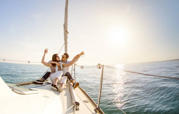 young couple in love on sail boat with champagne at sunset - happy people lifestyle on exclusive luxury concept  - soft backlight focus on warm afternoon sunshine filter - fisheye lens distortion - enjoying wealthy life imagens e fotografias de stock