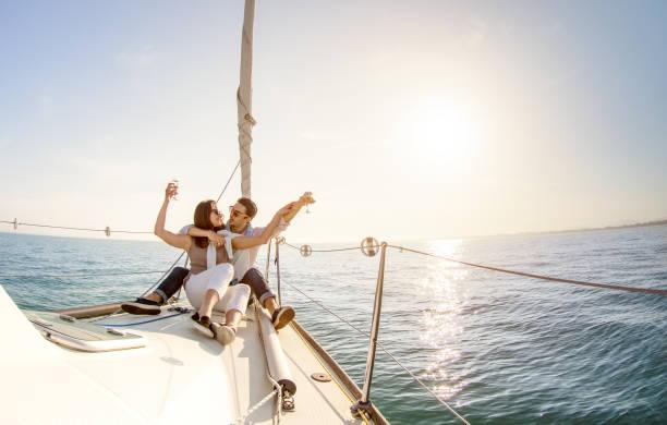 ungt par i kärlek på segelbåt med champagne i solnedgången - glada människor livsstil på exklusiv lyxig koncept - mjuk bakgrundsbelysning fokus på varm eftermiddag sunshine filter - fisheye linsförvrängning - katamaran bildbanksfoton och bilder