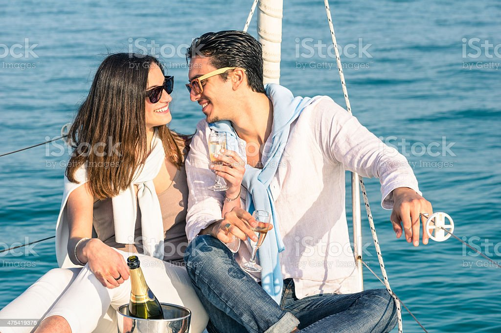 Young couple in love on sail boat with champagne bottle stock photo
