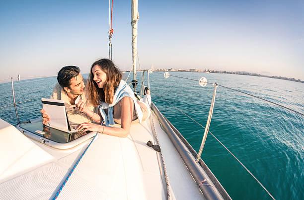 Jeune couple dans l'amour sur le bateau à voile s'amusant avec tablette - Photo