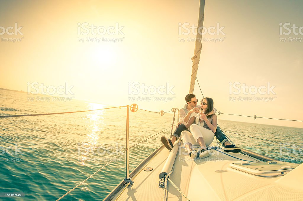 Young couple in love on sail boat with champagne at sunset - Happy...