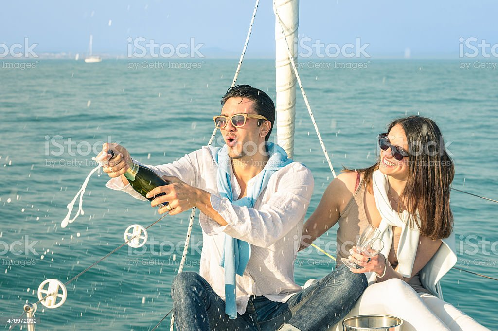 Young couple in love on sailing boat with champagne wine stock photo