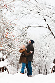 Young couple in love on the bridge in the park in winter