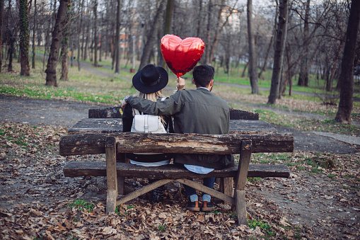 Couple in love sitting in the park on valentine's day and having heart-shaped helium balloon