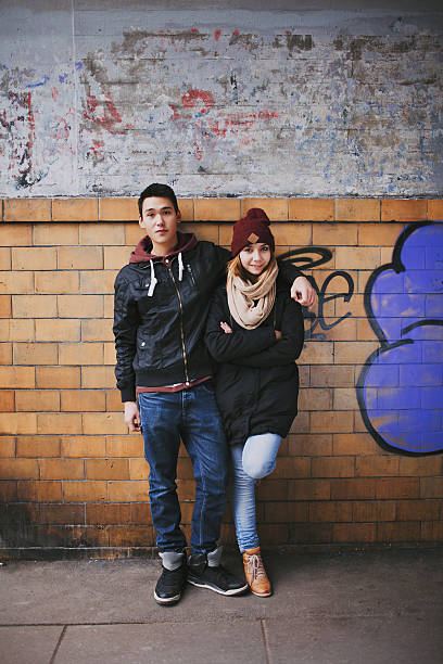 Young couple in love posing for a portrait Full length portrait of handsome young man standing with his beautiful girlfriend leaning against a wall. Mixed race teenage couple posing together outdoors cute teen couple stock pictures, royalty-free photos & images