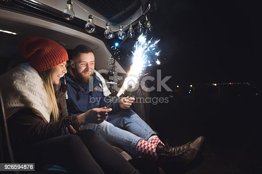 Young couple in love sitting in car open trunk