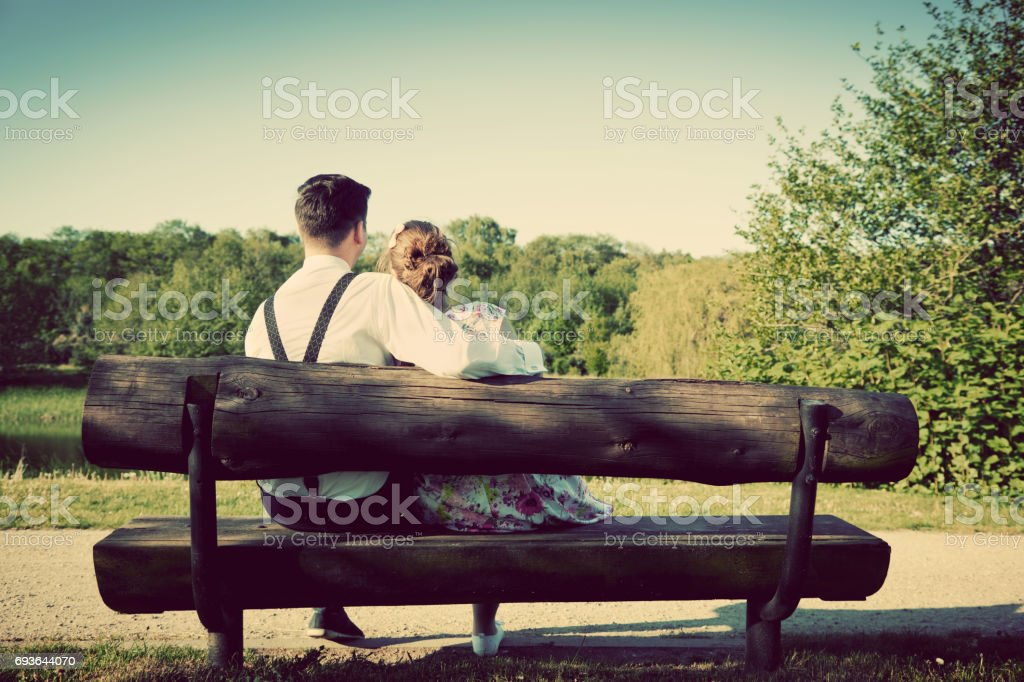 Young couple in love sitting together on a bench in summer park. Man...