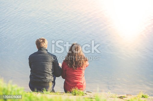 Young couple in love sitting on the beach and looking at sea