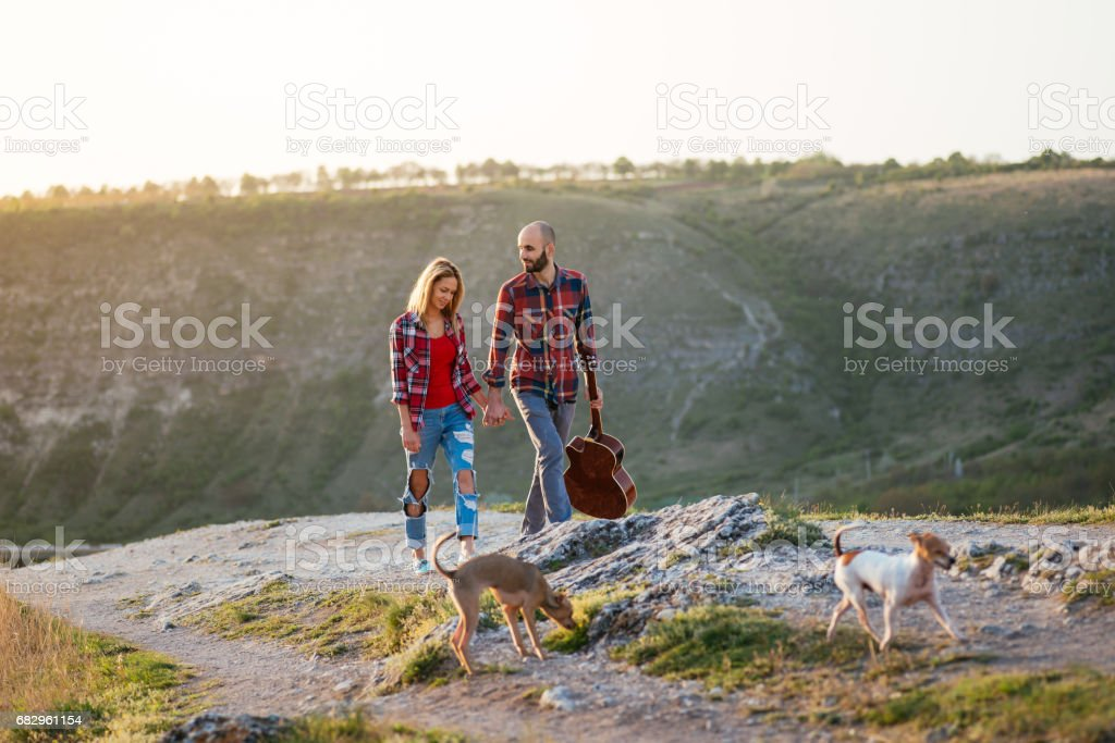 Young couple in love sitting on the park  while these young guitar playing guitar in sunset time. foto de stock royalty-free
