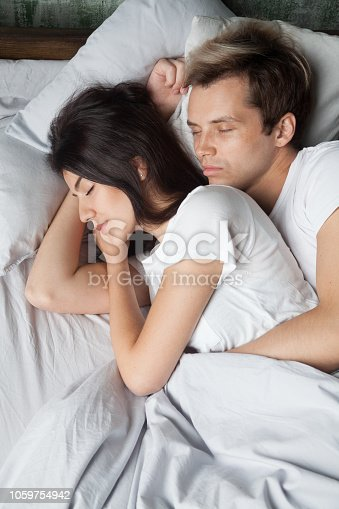 504371332istockphoto Young couple in love sleeping and embracing in bed 1059754942