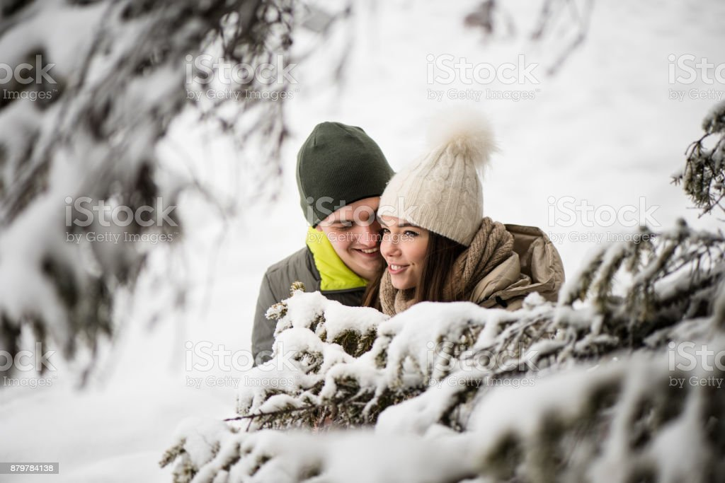 Young couple in love - snowy background. stock photo