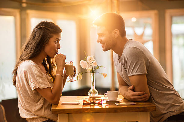 young couple in love spending time together in a cafe. - biriyle çıkmak stok fotoğraflar ve resimler