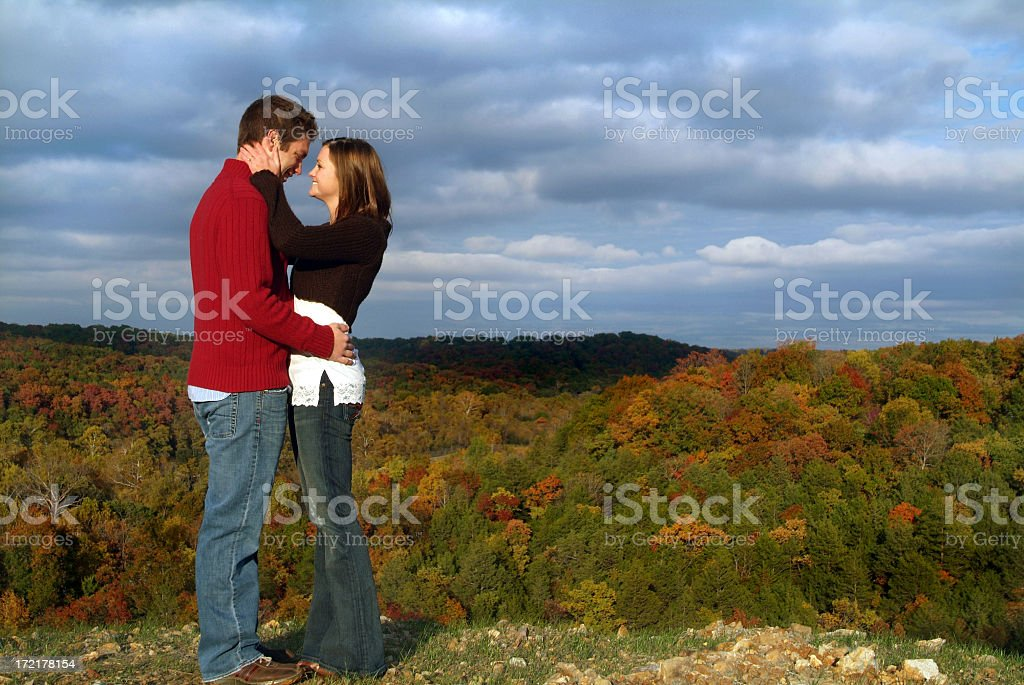 Young Couple in Love Standing on a Ridge in Autumn stock photo