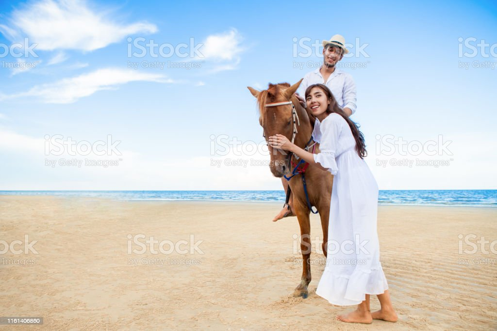 Young couple in love walking with the horse at sea beach on blue sky...