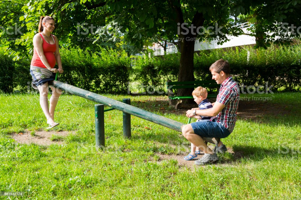 Young couple in park playing with little boy on swing...woman is pregnant royalty-free stock photo