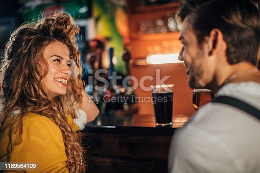 Young couple drinking beer in pub