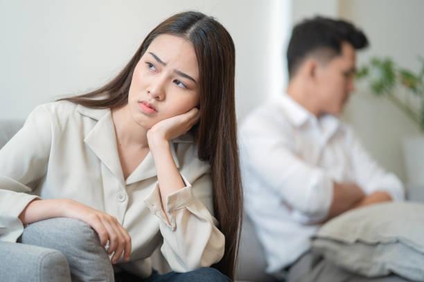 Joven pareja en pelea en casa.tristeza joven asiática mujer sentada en el sofá con novios.problemas de relación entre parejas y problemas de comunicación concepto - foto de stock