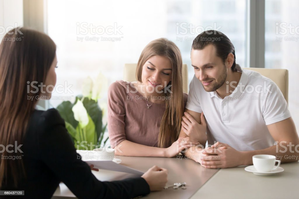 Young couple in real estate agency office meeting with agent stock photo