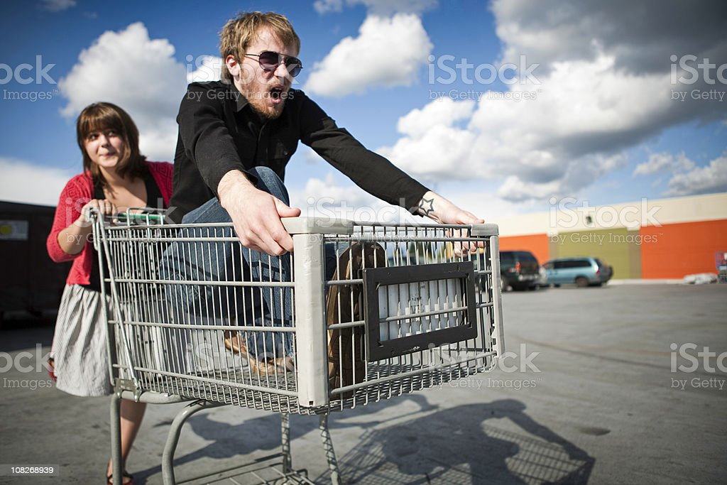 Young Couple in Shopping Cart Race royalty-free stock photo