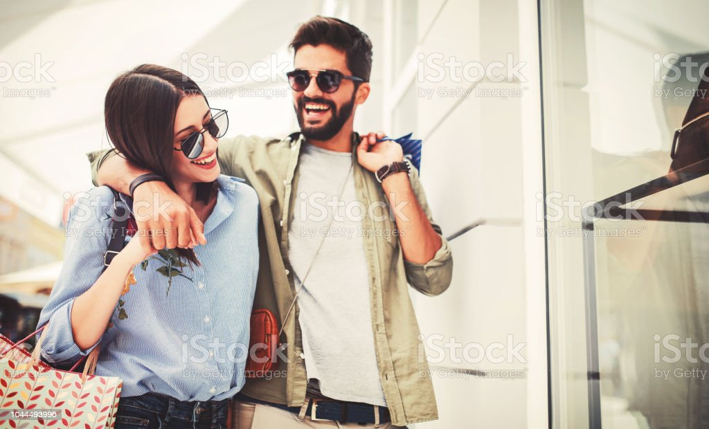 Young couple in shopping. Consumerism, love, dating, lifestyle concept stock photo