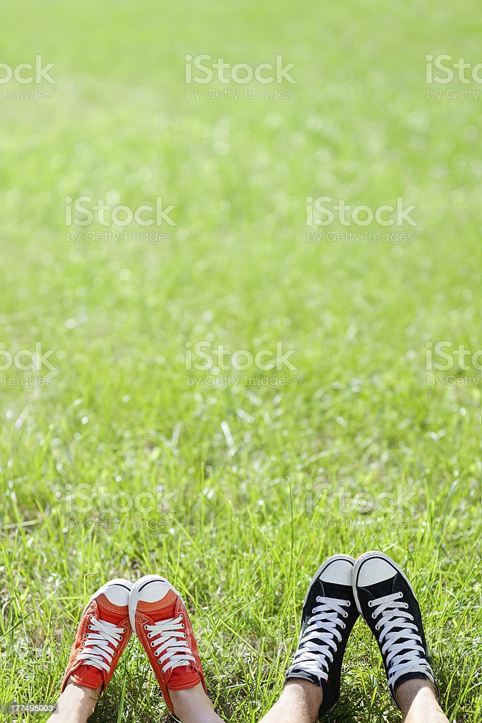 Young couple in sneakers on the green grass royalty-free stock photo