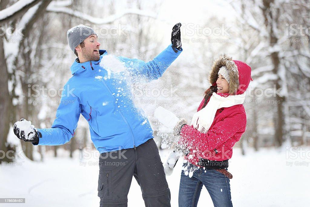Jeune couple dans la bataille de boules de neige - Photo