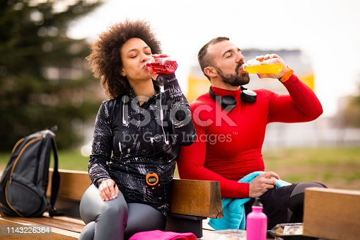 Young athletic couple hydrating themselves while taking a break after exercising in a city park.