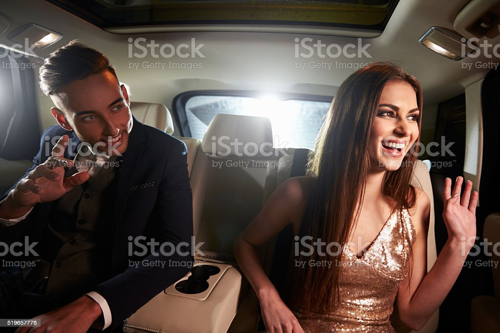 Young couple in the back of a limo looking out of stock photo