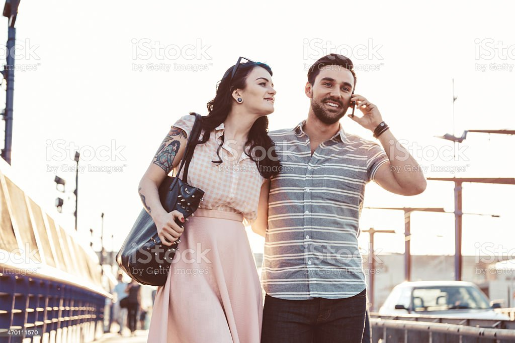 Young couple in the city, man talking on cell phone Happy young couple walking down the street in the city at sunset. Man talking on cell phone, woman has tatoo on her arm. 2015 Stock Photo