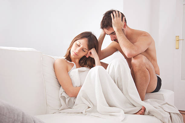 Young couple in the couch having conflict problem Sad couple faces erectile dysfunction stock pictures, royalty-free photos & images