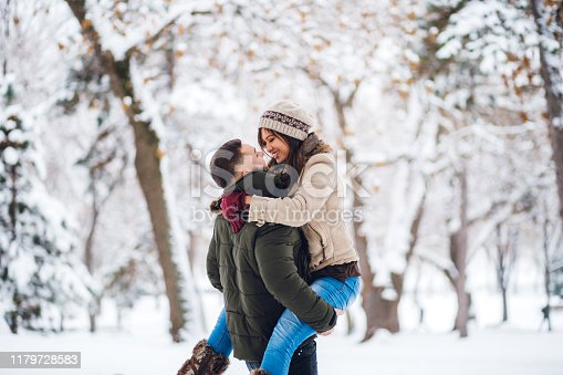 Young Caucasian cute loving couple in the snow. Man holding his girlfriend in arms.