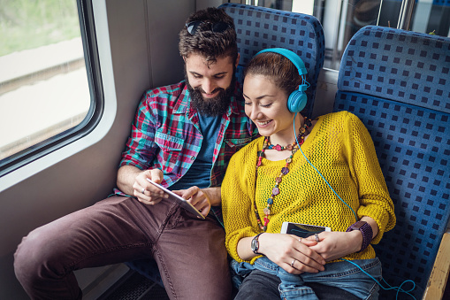 Attractive happy couple listening to music and browsing on the tablet while travelling