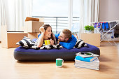 Happy young couple lying on inflatable mattress in their new apartment, flirting over morning coffee. Cardboard boxes on the floor.