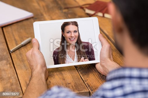 Closeup of a woman talking through video chat on tablet. Young man communicating with his girlfriend on tablet in video chat. Young man looking at screen of tablet and talking with a woman trought webcam.
