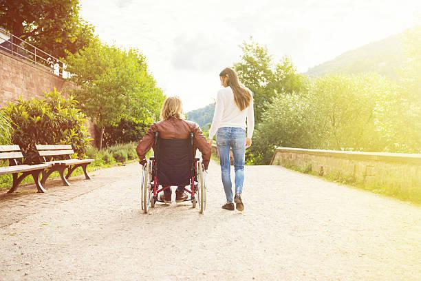 young couple in wheelchair strolling in the park - sommerferien baden württemberg stock-fotos und bilder
